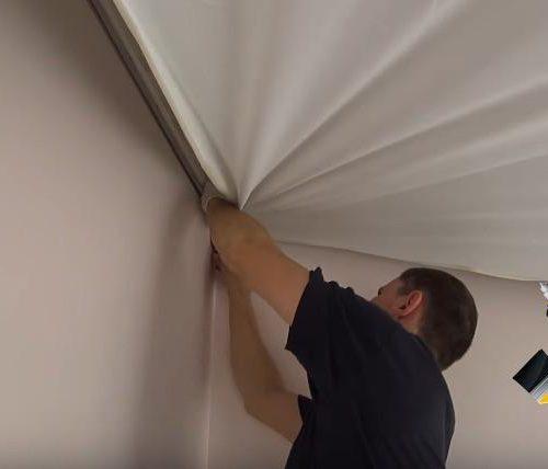 Мастер Сергей натягивает потолок в комнате