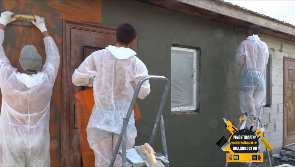Рабочие занимаются штукатуркой стен фасада в пригороде Владивостока